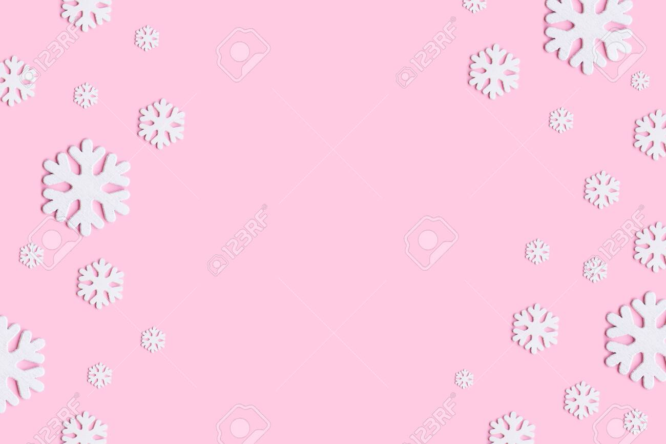 128902282 christmas wallpaper winter composition of snowflakes on pastel pink background flat lay top view