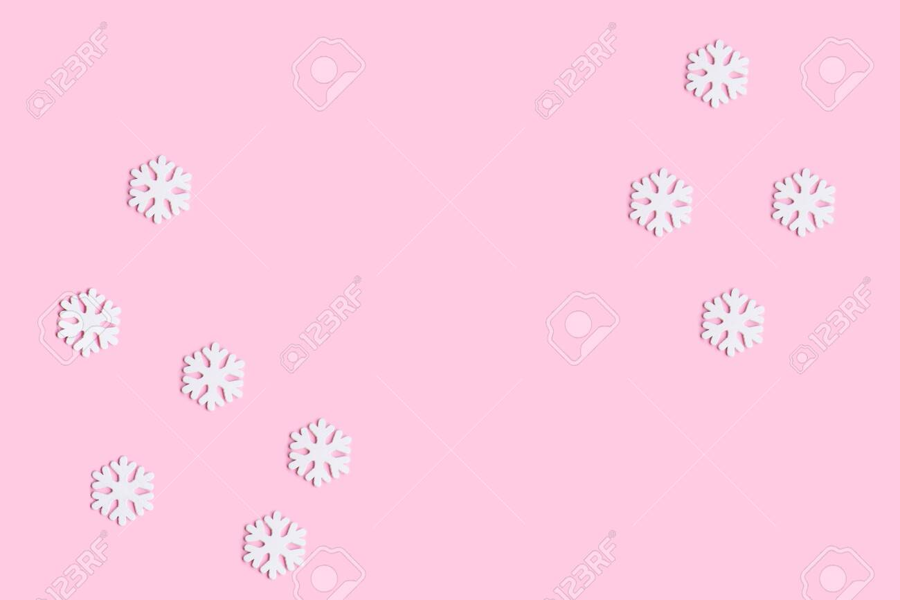 128902306 winter composition of snowflakes on pastel pink background flat lay top view christmas wallpaper