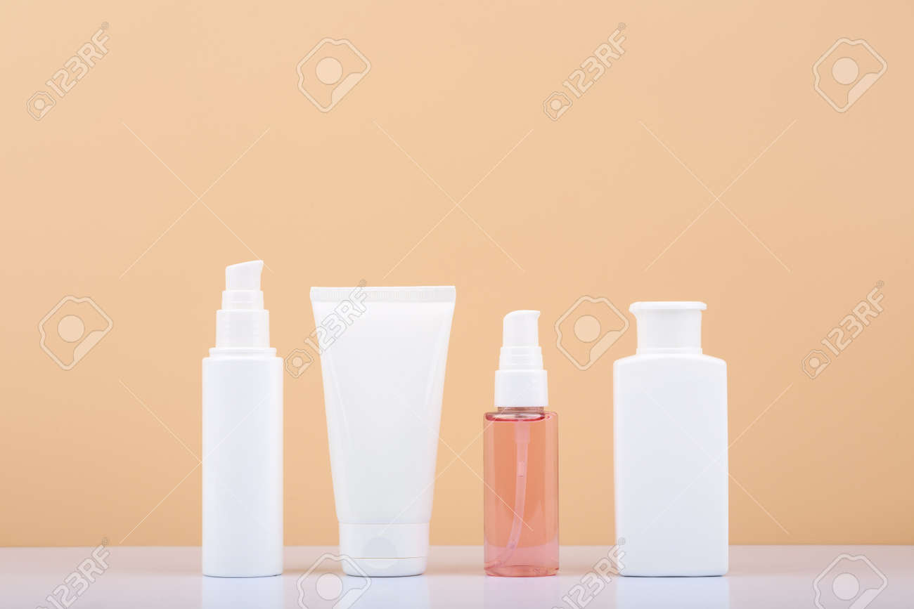Skin care products in a row on white table against beige background. Beauty and cosmetic concept - 166585631