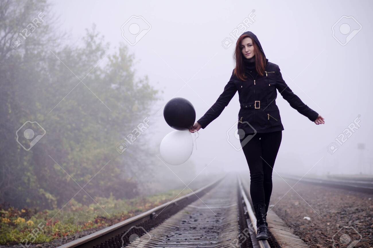 Lonely girl in black clothing walking on the rails in a fog. She holds a black and white balloon in her hand and it fly away. Concept of choice, target, good and evil, way in life - 138897308