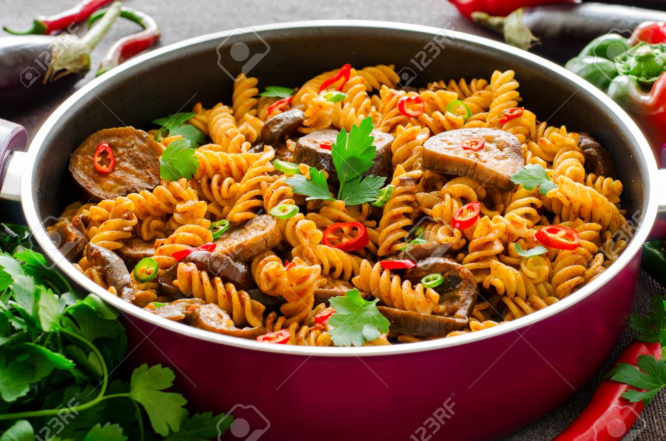 Mediterranean Eggplant Pasta In Pot With Tomatoes, Pepper And Parsley On  Grey Background. Stock