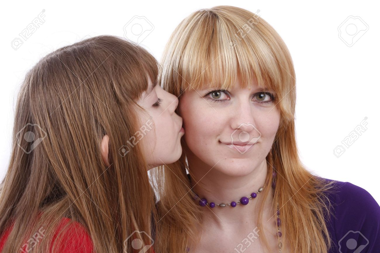 Girl is kissing woman. Daughter's kiss. Daughter kissing her happy mother.  Isolated on white in studio. Stock Photo - 4880253