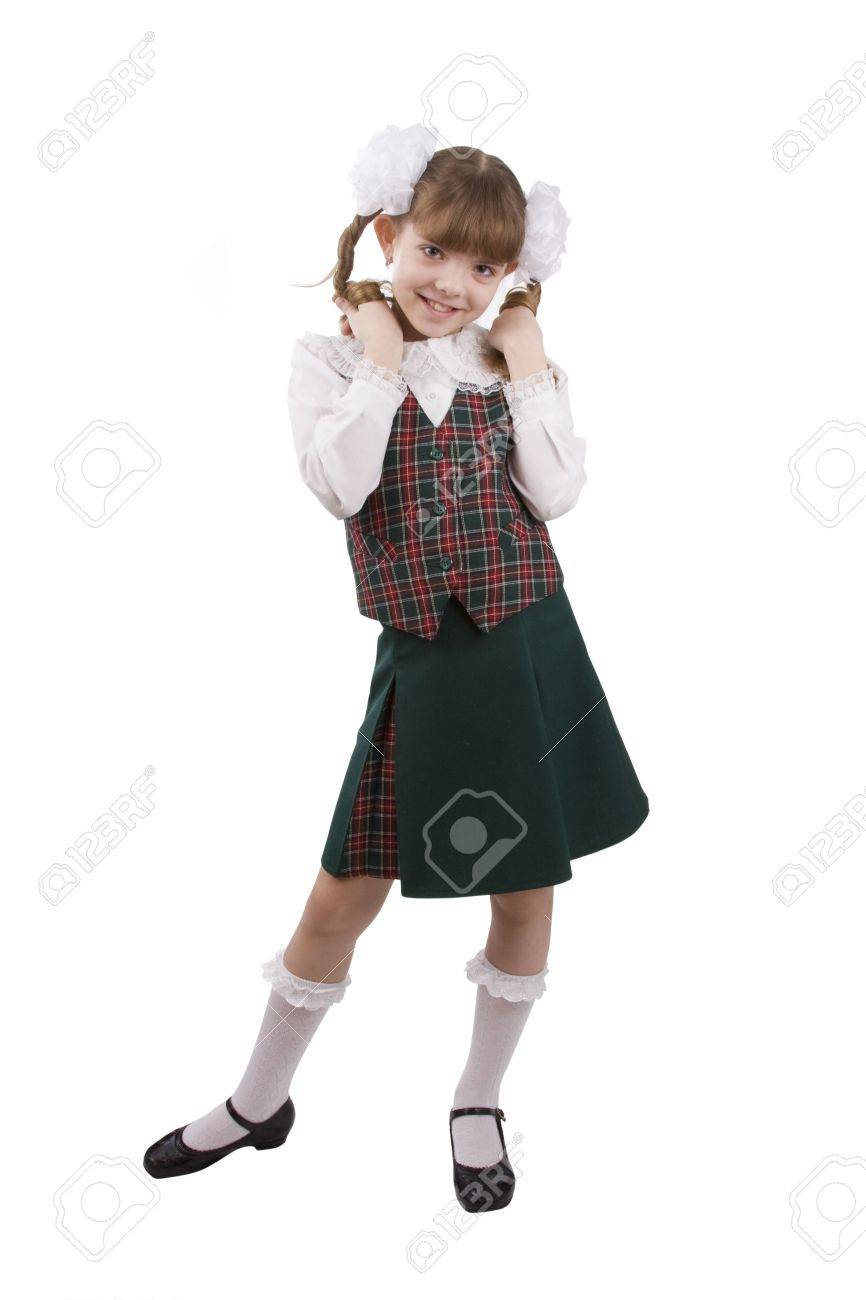 Little girl in school uniform. Pupil is trifling with hair. Isolated on white in studio. Stock Photo - 5410617
