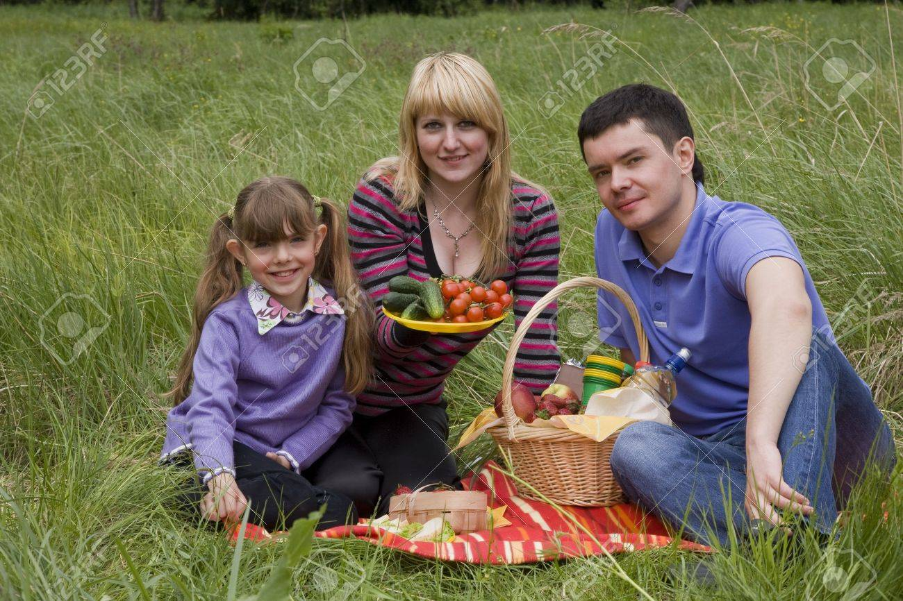 Family having picnic in park. Parents and child on picnic in the forest. Mother, father and daughter relaxing. Woman is holding vegetables. Stock Photo - 5441127