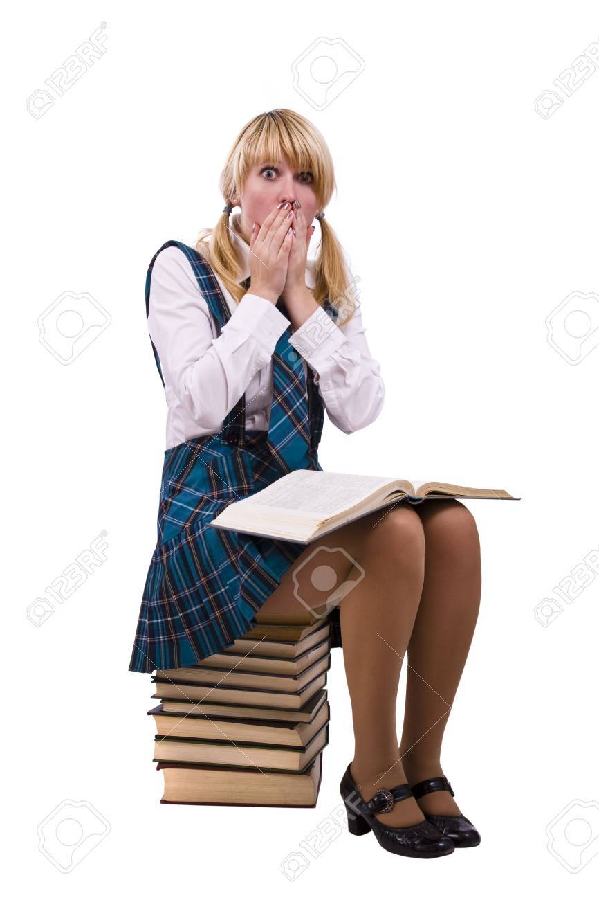 Senior high school student in uniform is sitting on the stack of book and study up. Young and beautiful schoolgirl  is wearing a traditional uniform is shocked by something. Stock Photo - 5999716
