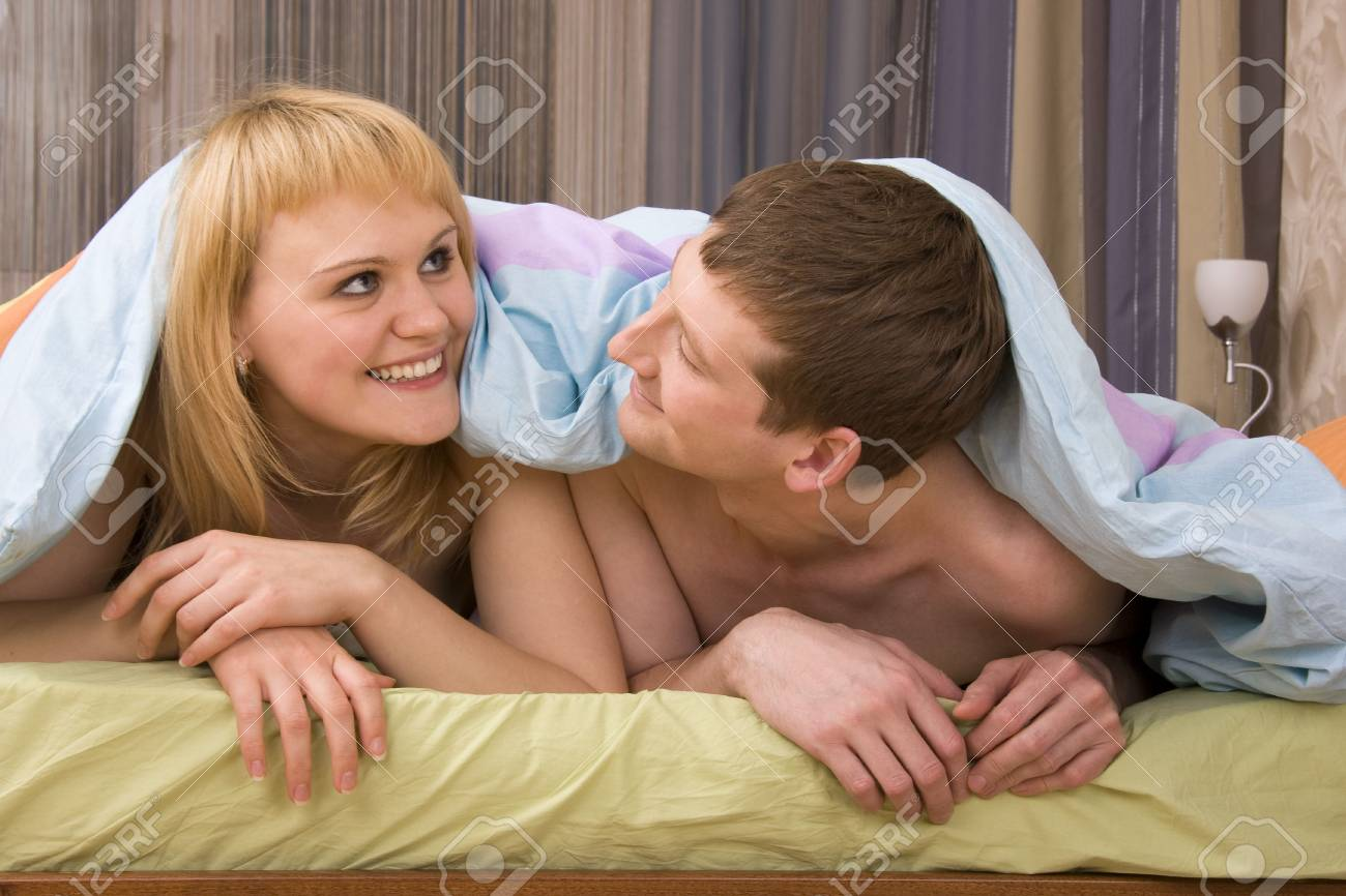 Young attractive happy amorous couple at bedroom. Woman and man are lying on bed. Loving female and male playing in the bed. Stock Photo - 6228057