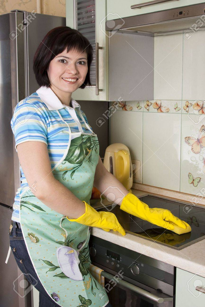 Young woman cleaning cooker at the kitchen. Smiling female washing stove top. - 6833912