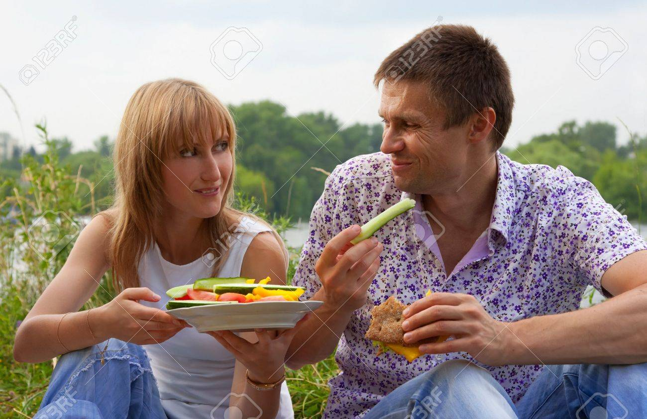Young happy couple eating together outdoors Stock Photo - 9511813