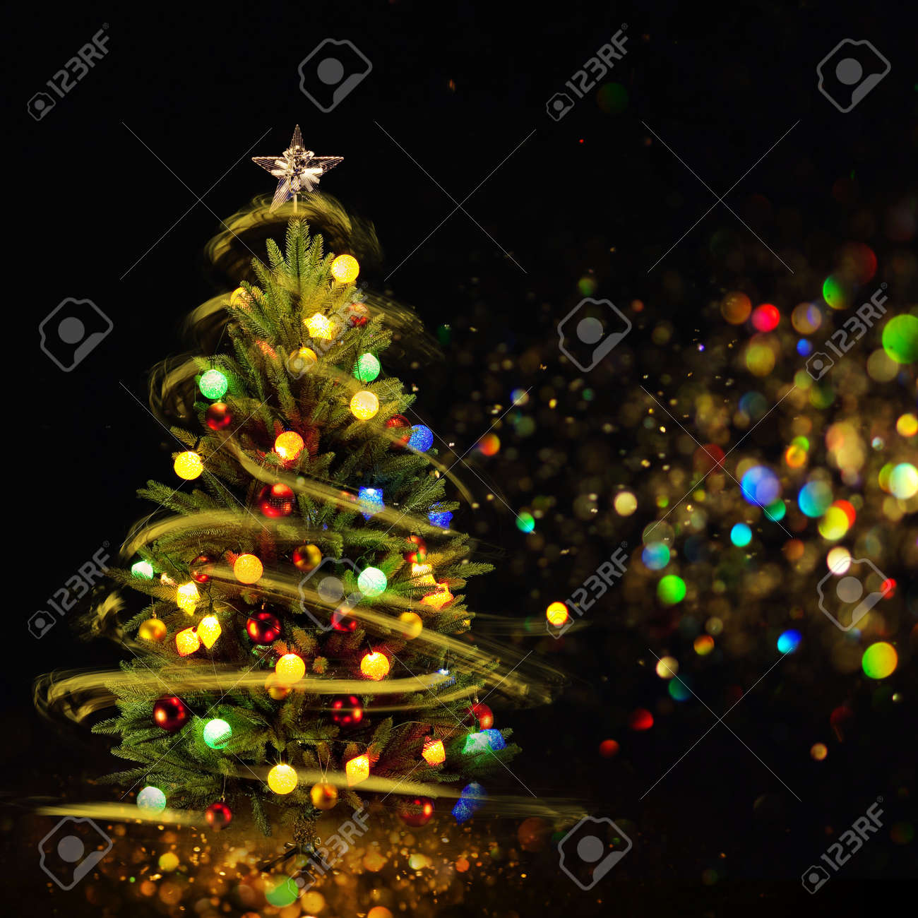 snow covered christmas tree with multi colored lights at night stock photo 66354008