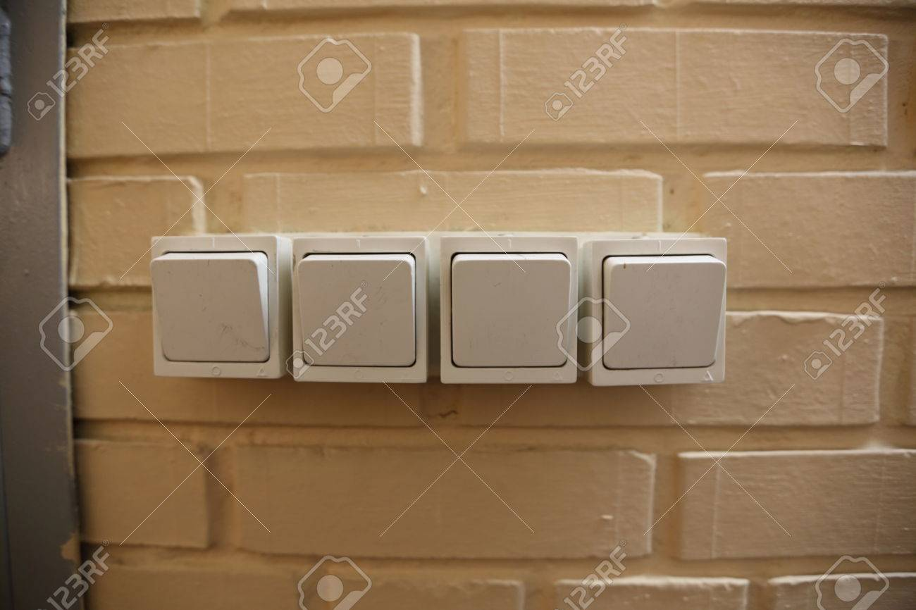 Four White Household Electric Switches On A Brick Wall Stock Photo ...