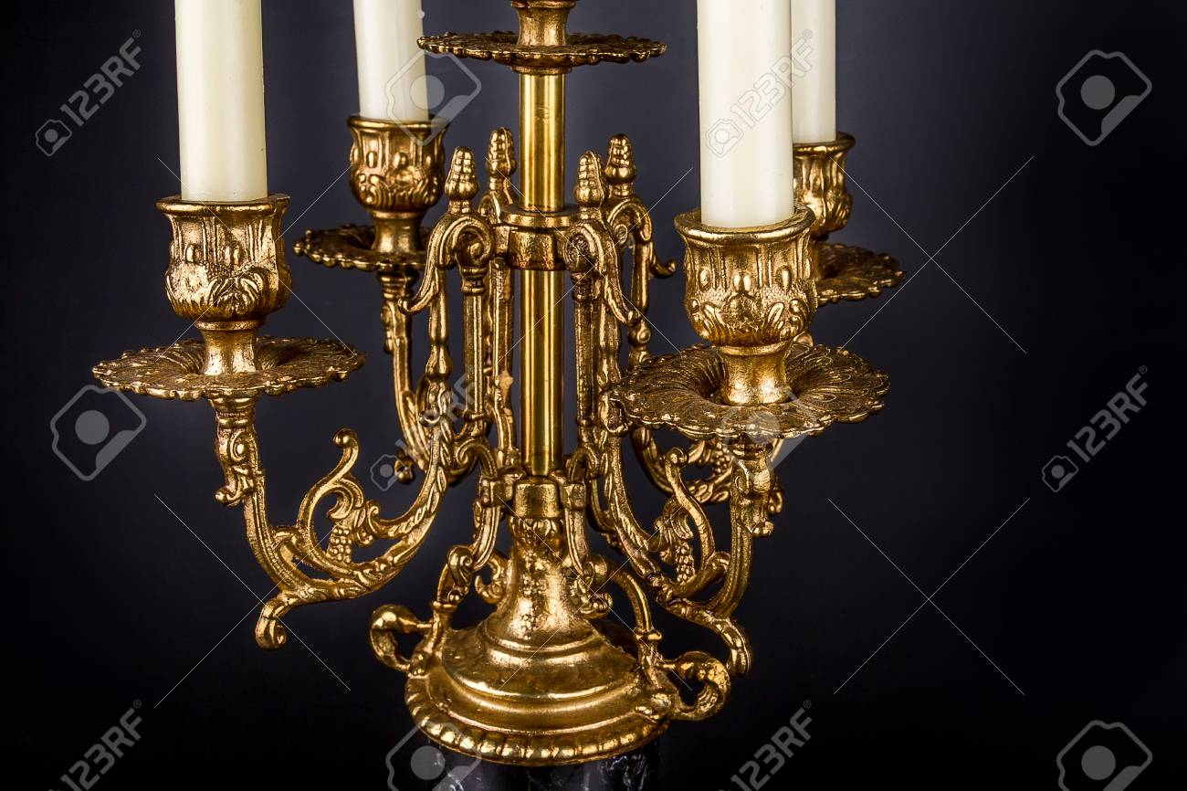 Antique bronze chandelier candle holder on a black background bronze and black marble