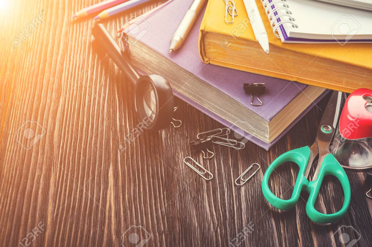 Frame of school supplies on a wooden table, space for your text,