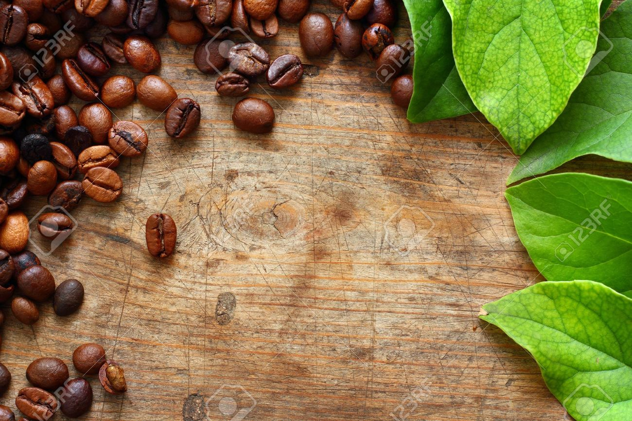 Coffee on wooden background with green leaves Stock Photo - 16776458