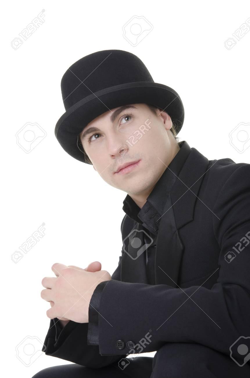 Foto de archivo - Hombre joven y atractiva en traje negro y sombrero está  mirando hacia arriba sobre fondo blanco 2ae96fc3b55