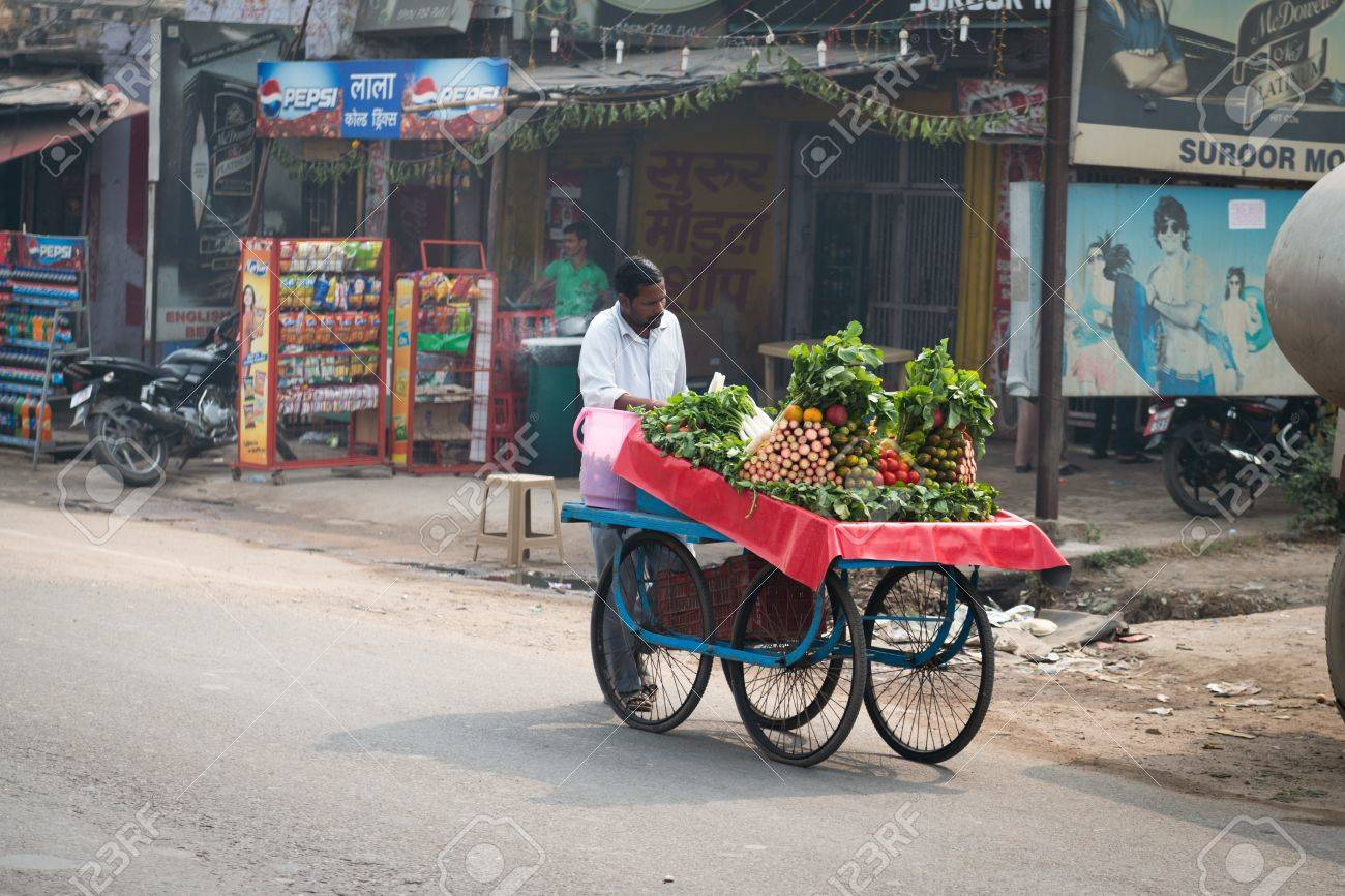 AGRA, INDIA - NOVEMBER 15: Asian mobile street vendor with fresh vegetable on typical messy street in central India on Nov 15, 2012 in Agra, India Stock Photo - 16870157