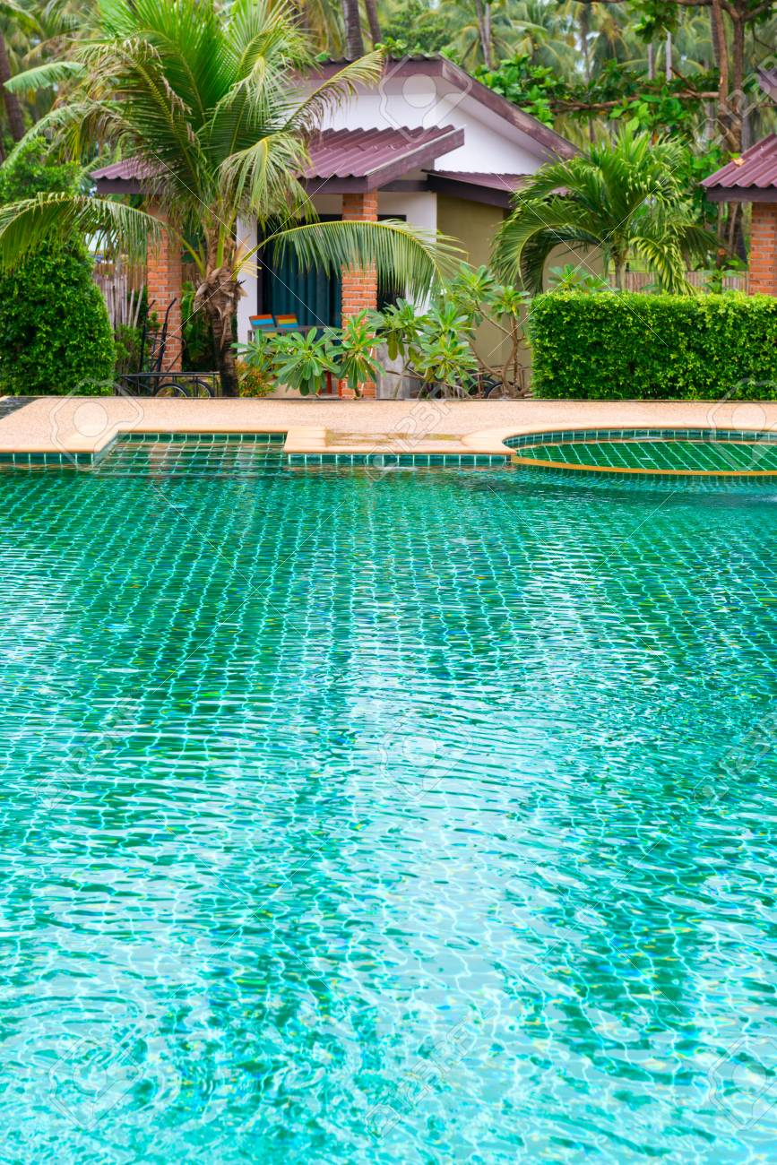 Swimming pool in a tropical hotel with green palms and bungalows..