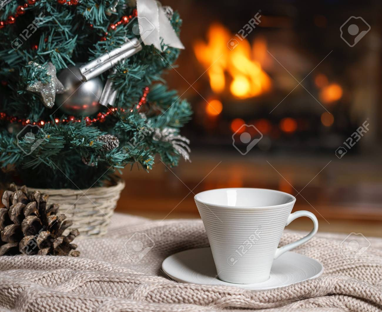 new year winter concept cup of tea or coffee woolen knitted things plaid and christmas decorations near cozy fireplace