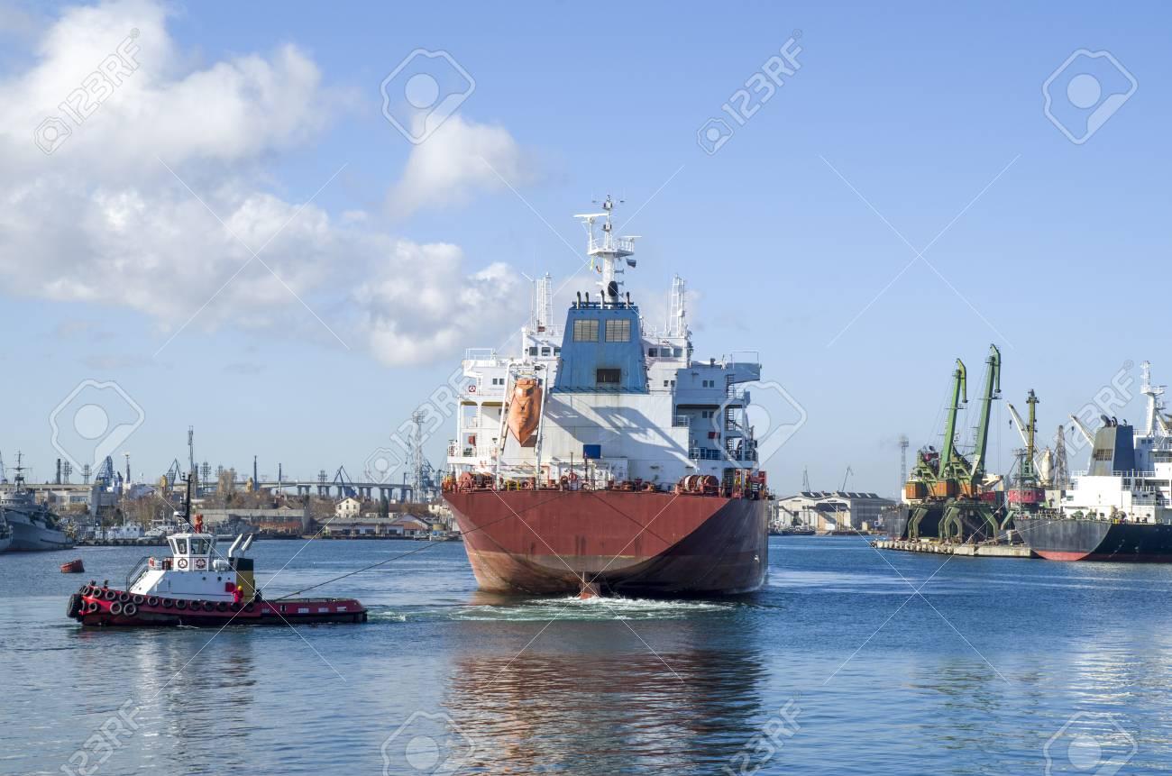 晴れた日の港にコンテナー船を曳...