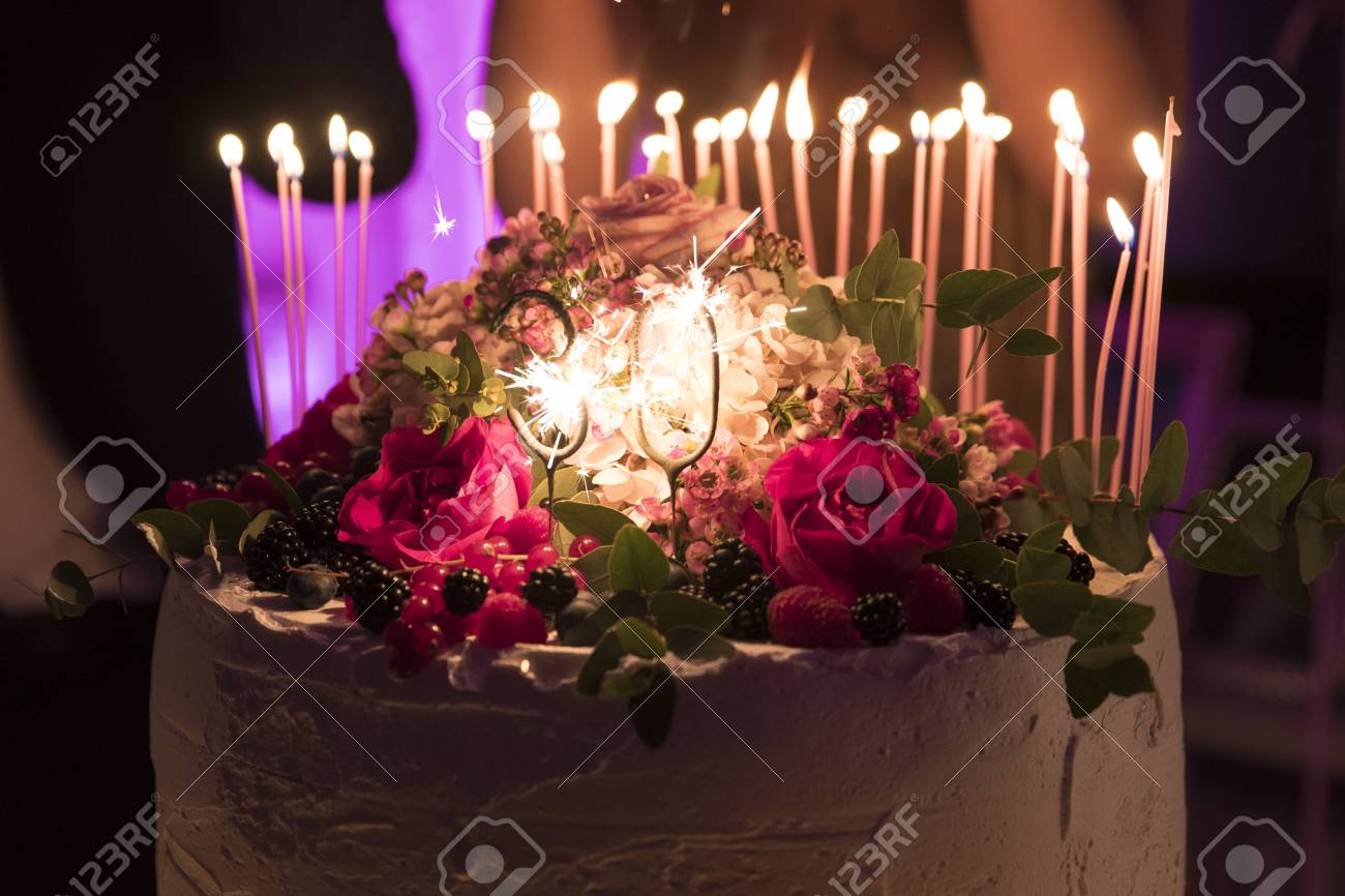 Beautiful Cake With Flowers On Top And Shimmering 30 Candle Stock Photo