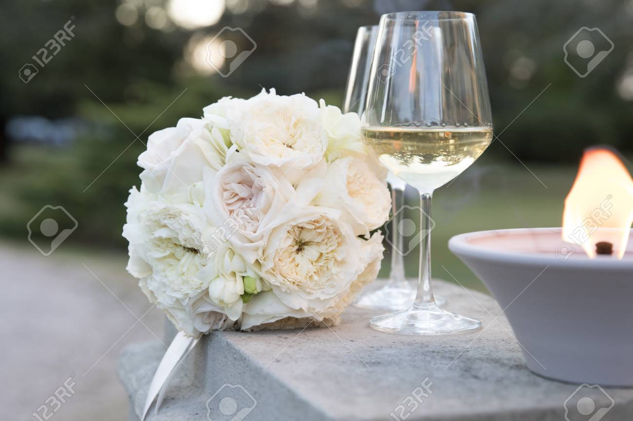 Pale Pink Wedding Bouquet Under Sunset Light With Two Glasses