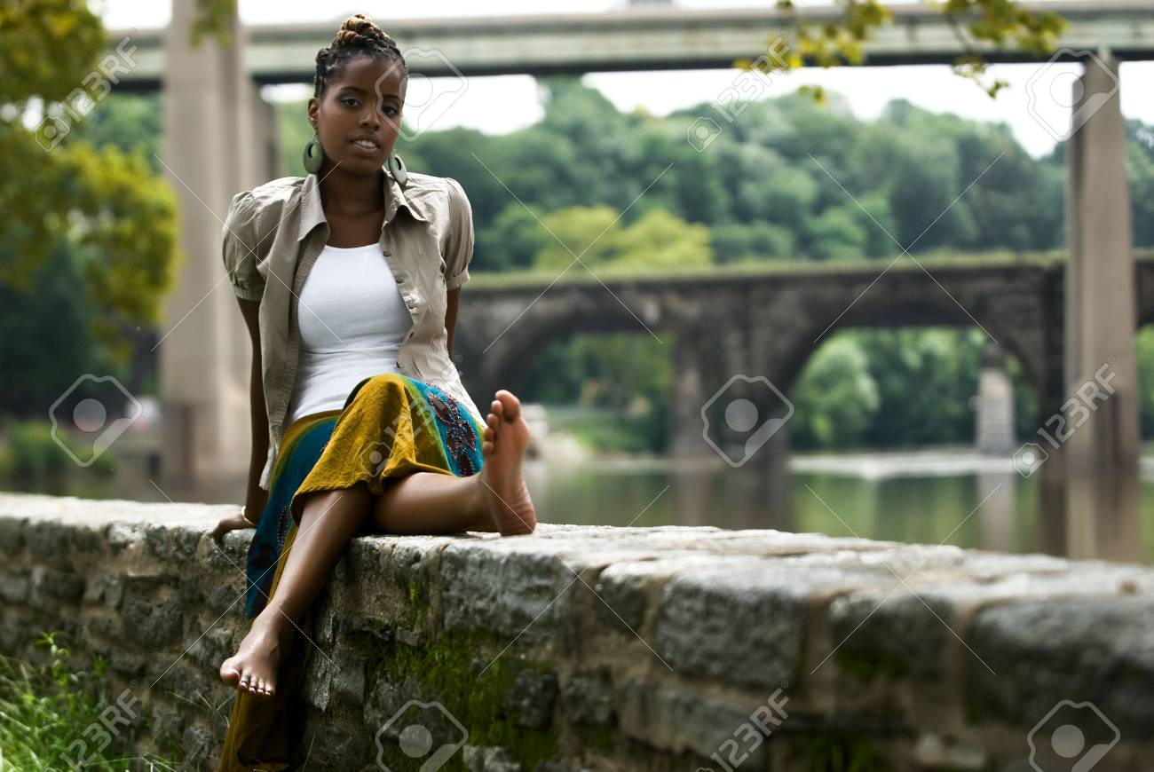 African American woman sits and relaxes by the river front Stock Photo - 5593602