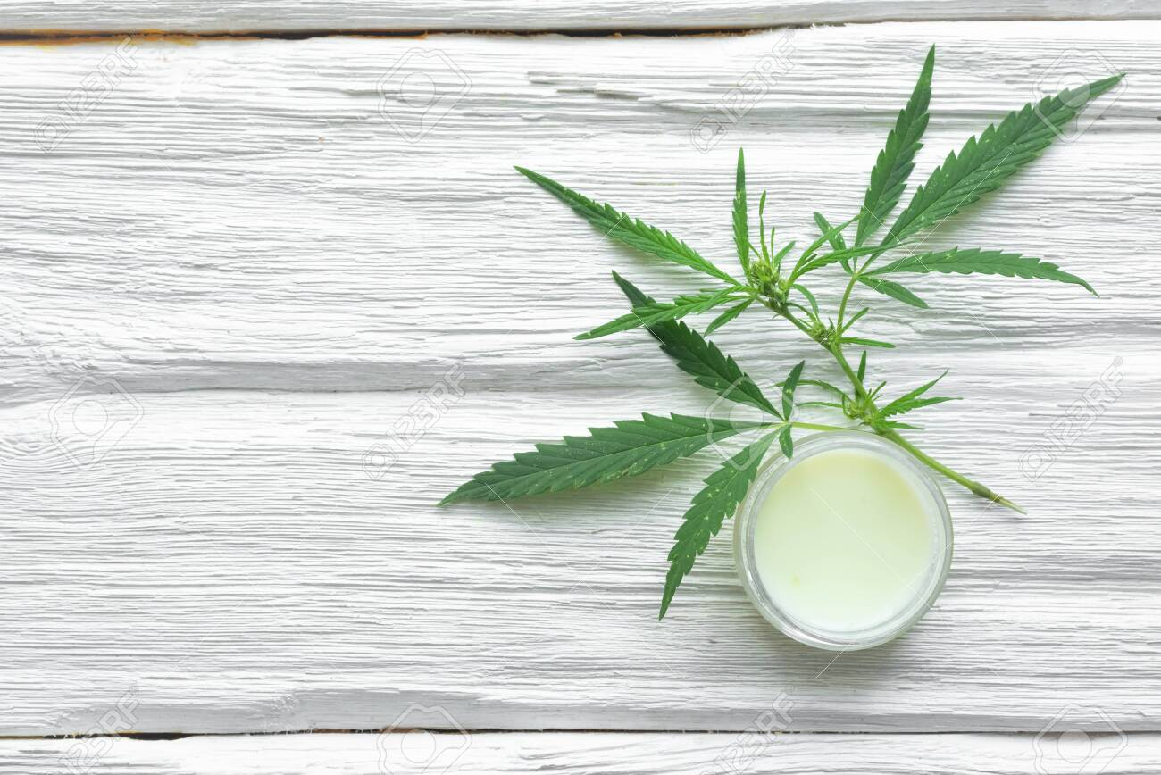 Cannabis cosmetic cream in a jar and a green plant leaf on a white wooden table background. Natural cosmetic. - 150049664