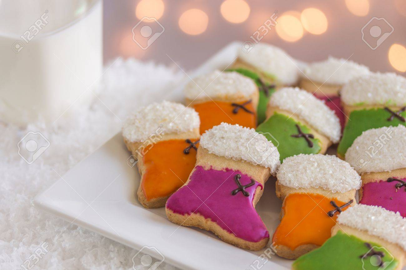 Orange, green and purple stocking cookies with sugar on plate