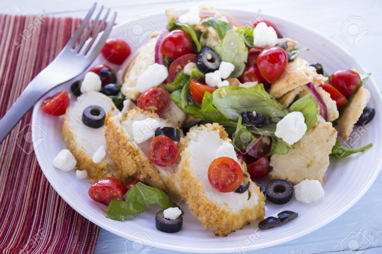 Salad with pita bread, cherry tomatoes, basil, red onion and kalamata olives served with breaded chicken and feta cheese Stock Photo - 18287402