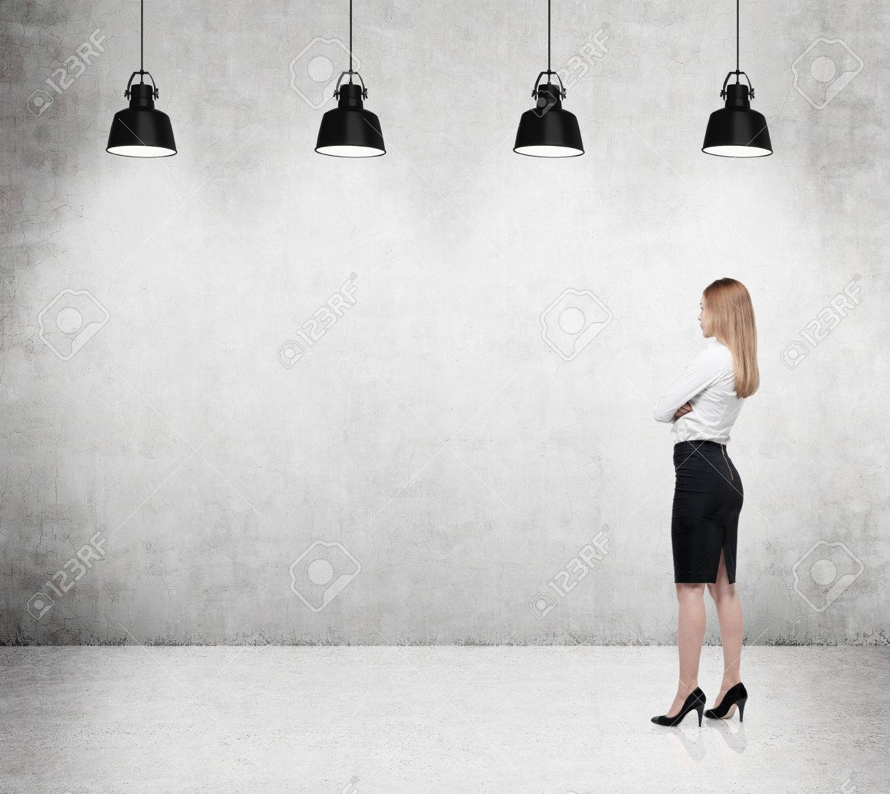 Businesswoman is looking at the concrete wall - 38330644
