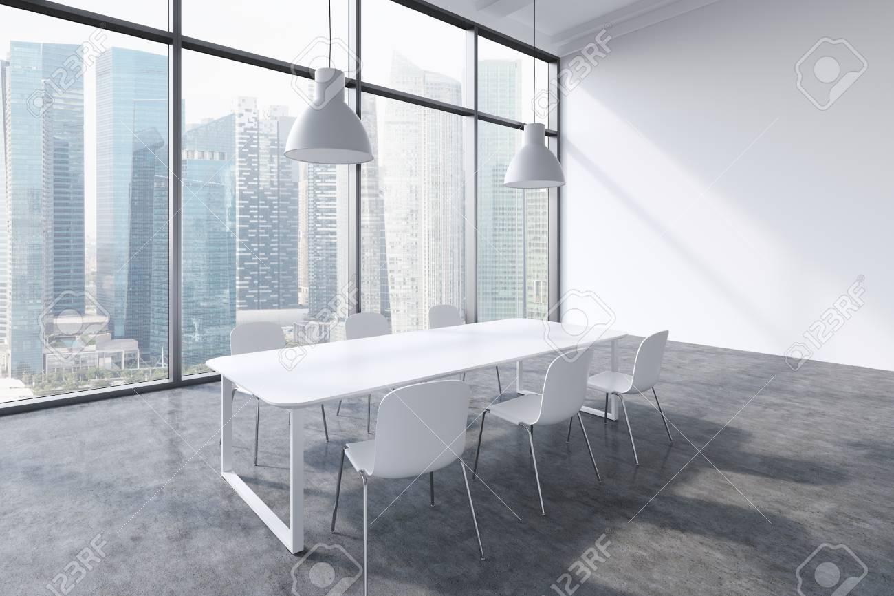 Una sala conferenze in un moderno ufficio panoramico con vista sulla città  di Singapore. Tavolo bianco, sedie bianche e due plafoniere bianche. ...