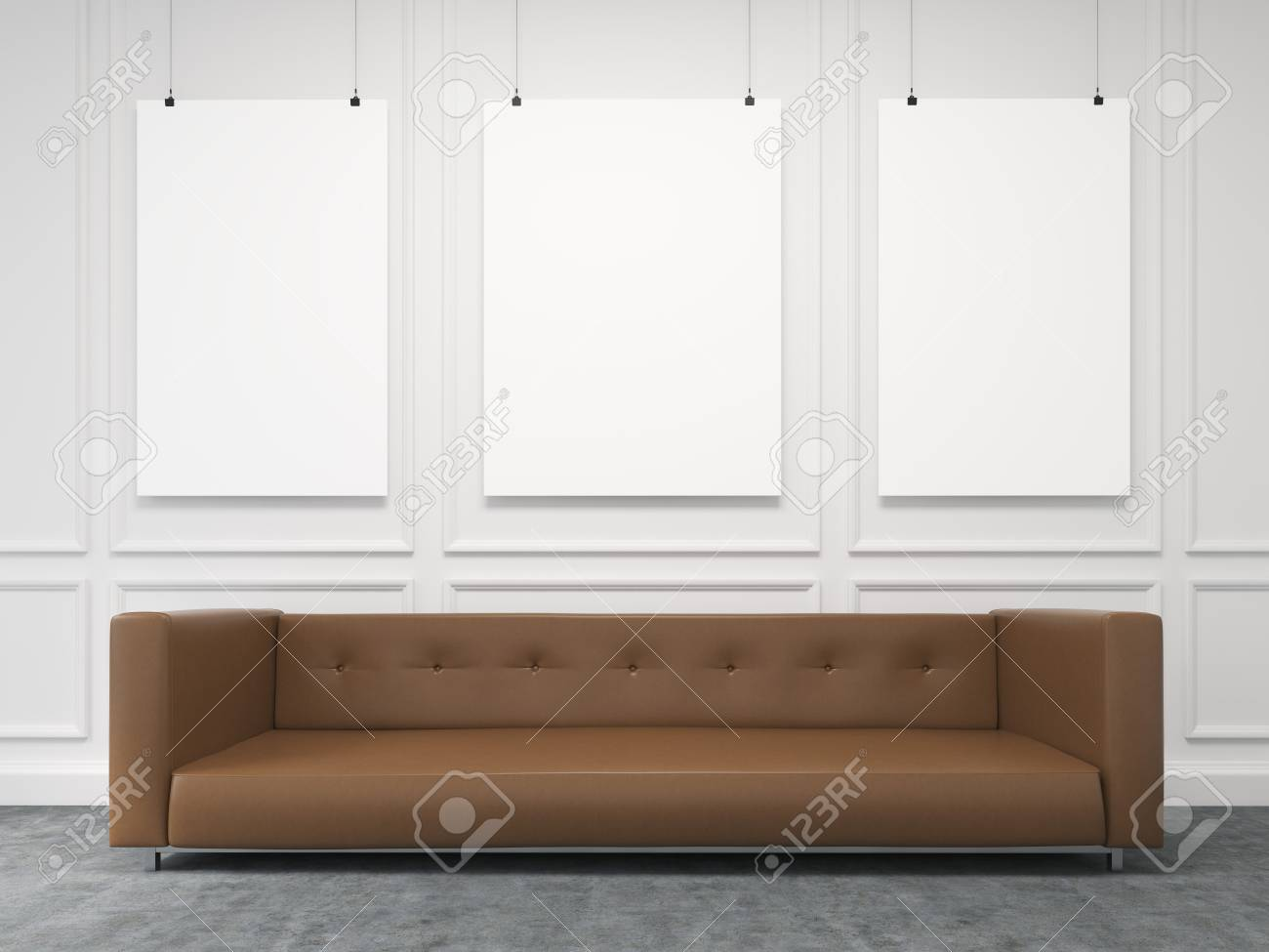 A long brown sofa standing at the white wall, three blank frames..