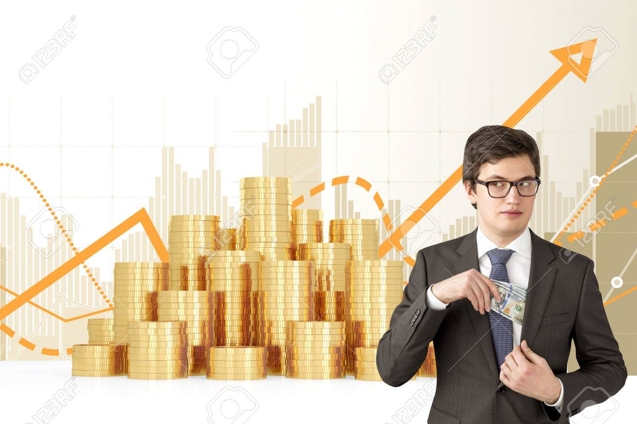 Man with sly look putting one hundred dollar banknotes into the chest pocket. Coins and graphs at background. Concept of getting rich. - 53210120
