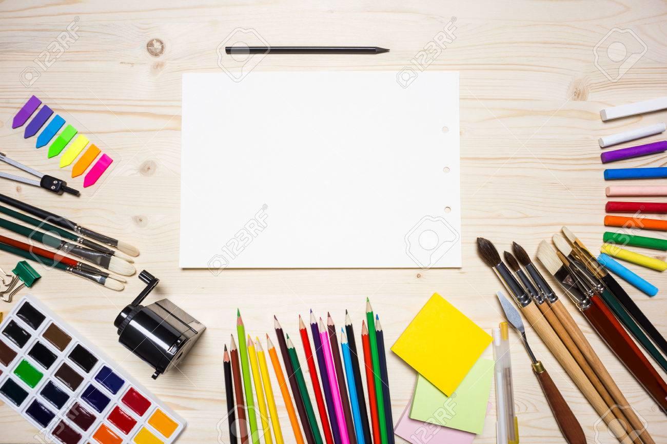 Vue de dessus bureau en bois clair avec un morceau de papier blanc