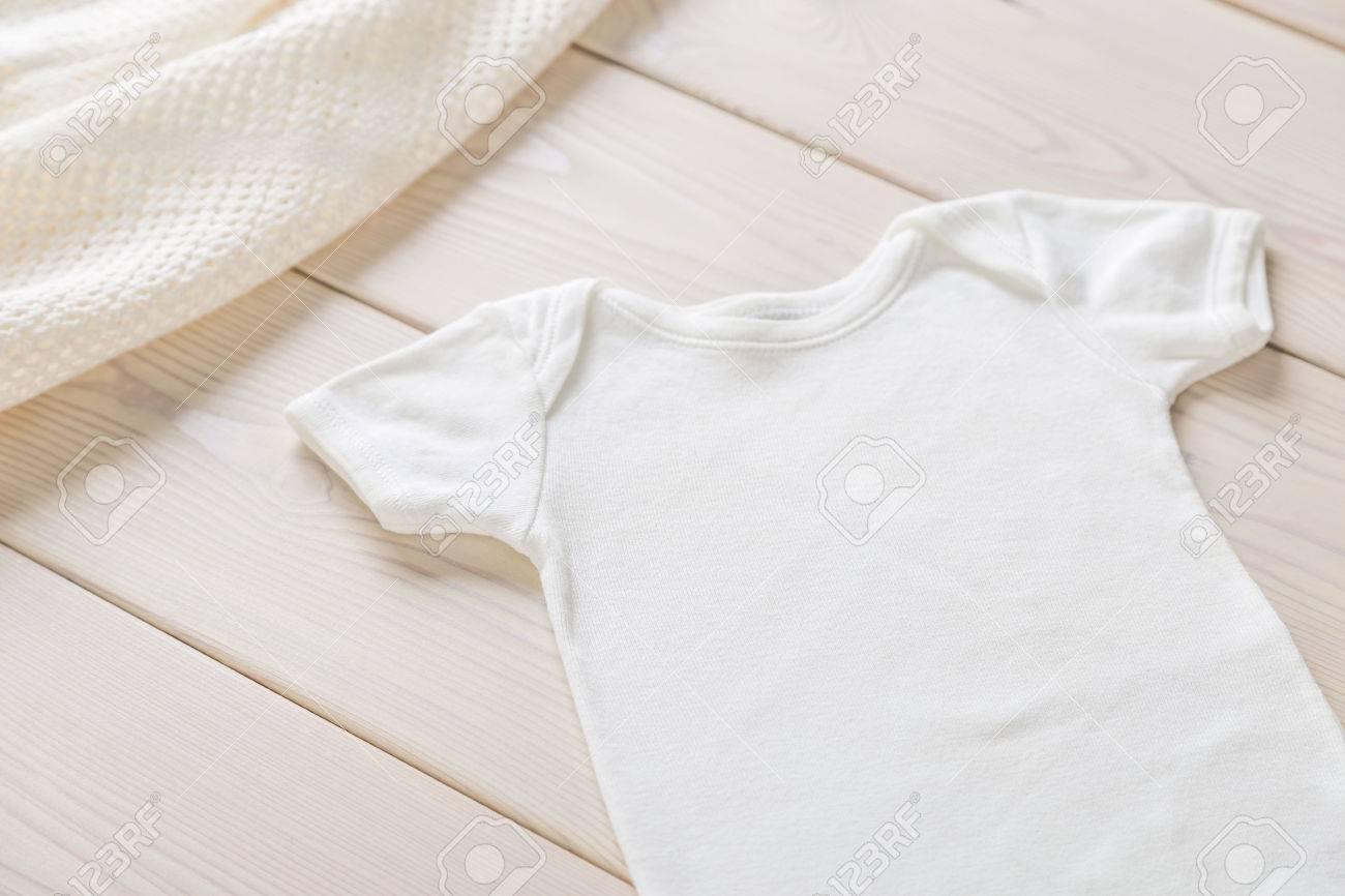 Blanc chemise de bébé sur le bureau en bois maquette banque d