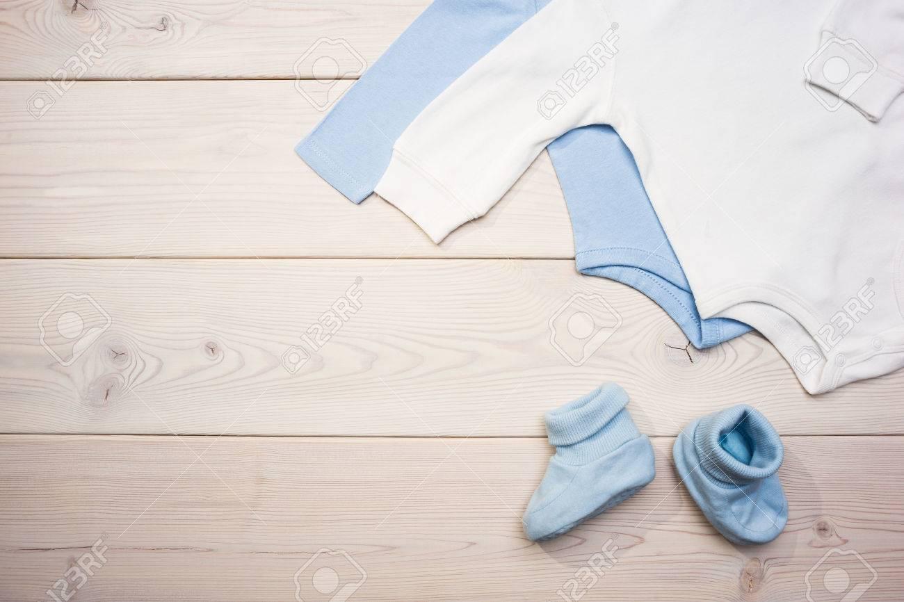 Vêtements de bébé bleu et blanc sur le bureau en bois clair