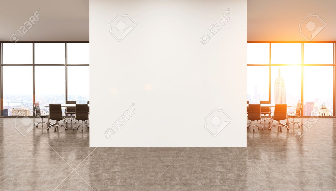 Muro bianco in centro di ufficio scrivanie e tavoli visto in