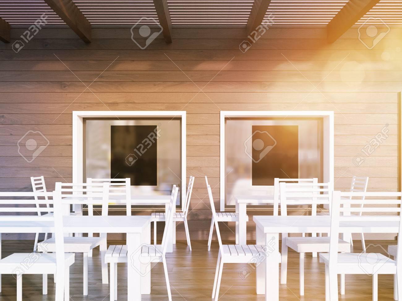 interior del restaurante con dos carteles negros en las ventanas mesas y sillas blancas