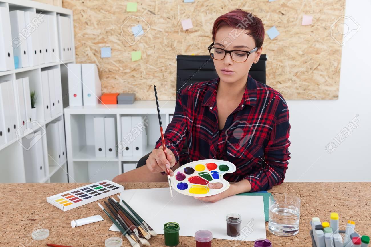 Bacheche Per Ufficio : Donna pittore prepara per la classe in un college. lei è seduta nel