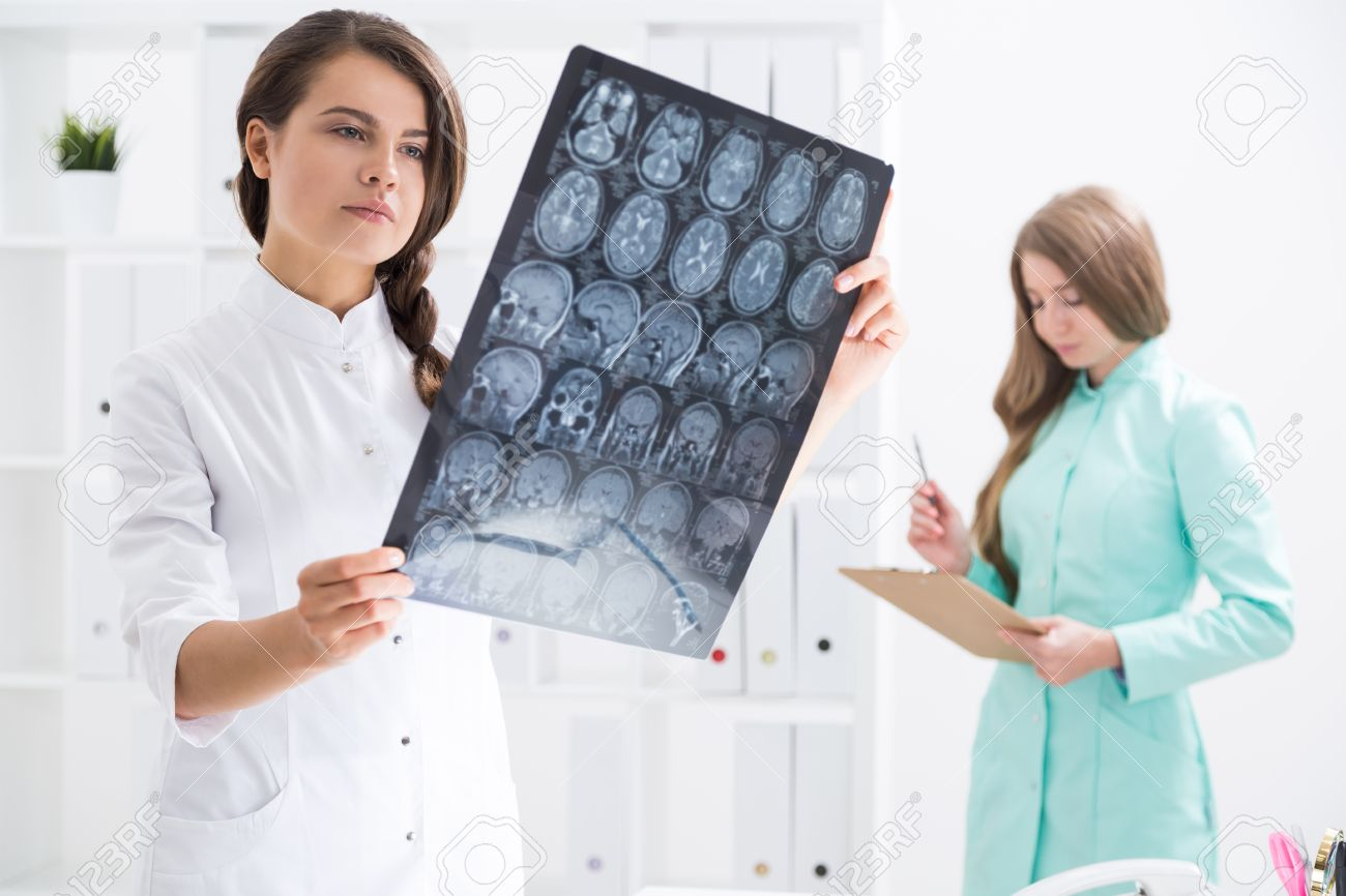Concentrated Woman With Braided Hair Is Examining Brain X Ray ...
