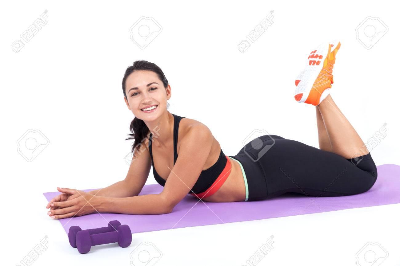 Sourire fille en vêtements de sport couché sur le tapis violet clair après  une teneur en session de formation intensive de ses progrès. Concept de ...