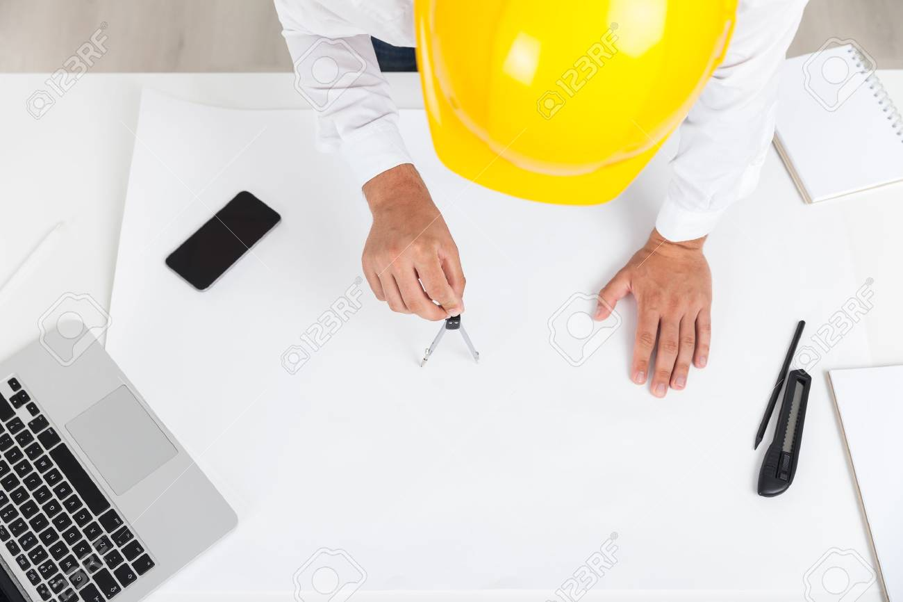 Top view engineer working with compass at new building blueprint engineer working with compass at new building blueprint smart phone and laptop on desk concept of design and construction malvernweather Image collections