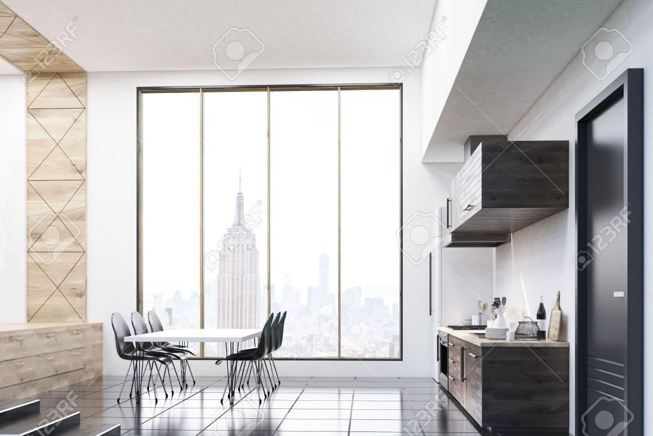 Estudio con grandes ventanas y zona de cocina. Gran mesa de comedor en el  centro de la habitación. Concepto de hogar contemporáneo. Las 3D