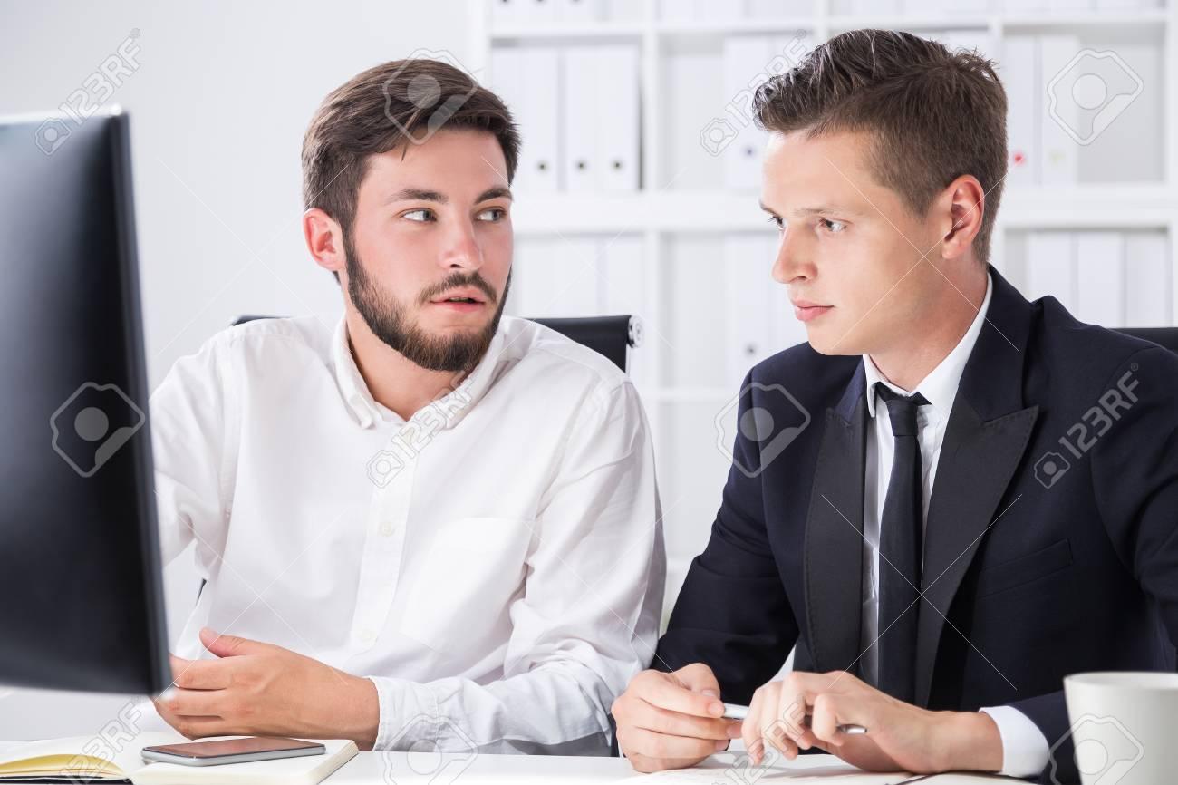 Posizione Scrivania Ufficio : Due partner sedersi al computer di scrivania in ufficio e parlare