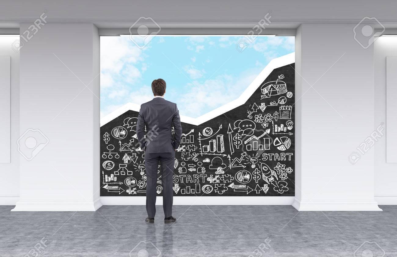 Vue arrière de l homme regardant au tableau noir avec des croquis