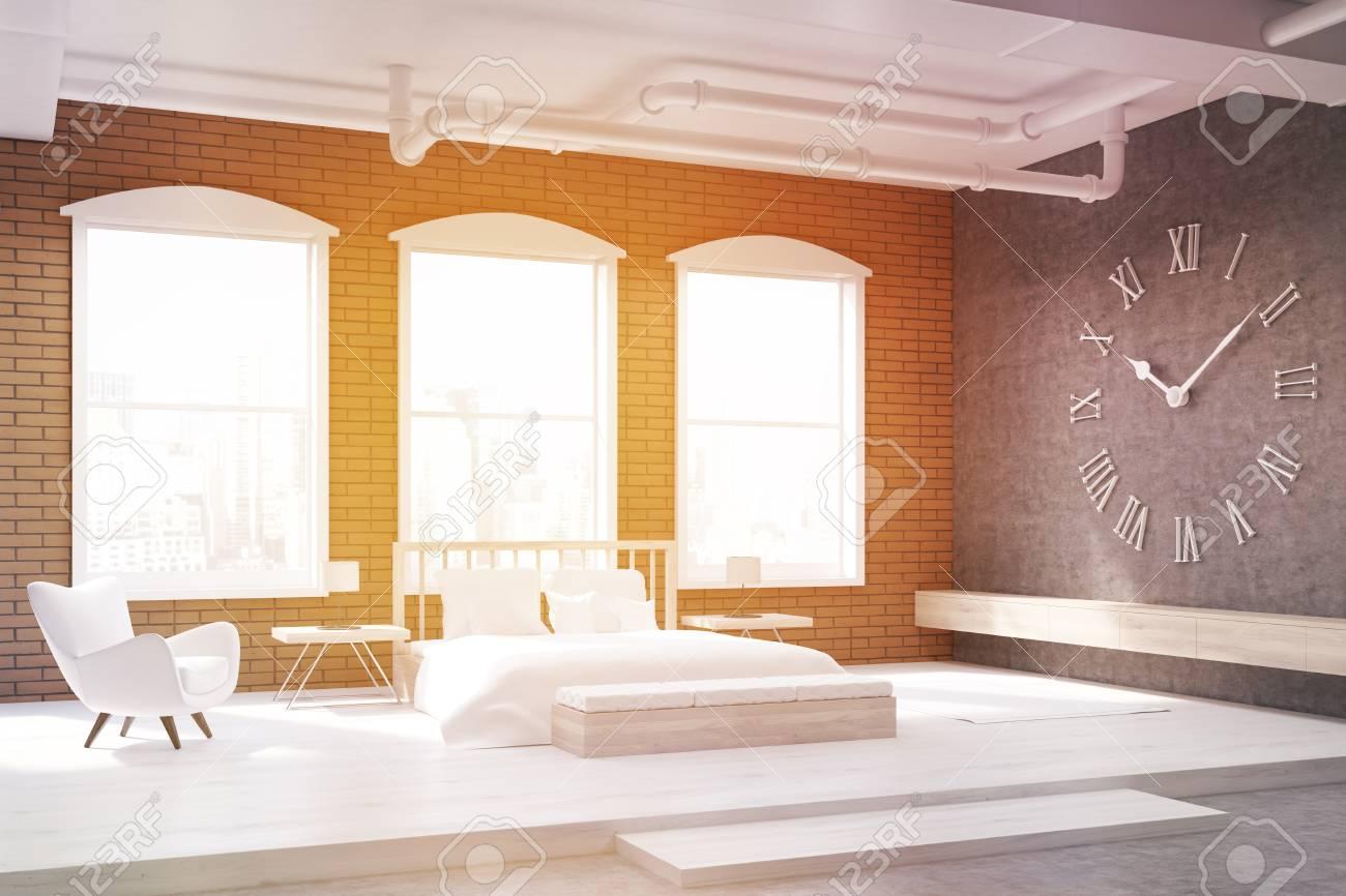 Sonnenbeschienenem Schlafzimmer Mit Großen Uhr Auf Graue Wand, Ein Riesiges  Bett Und Einem Sessel.
