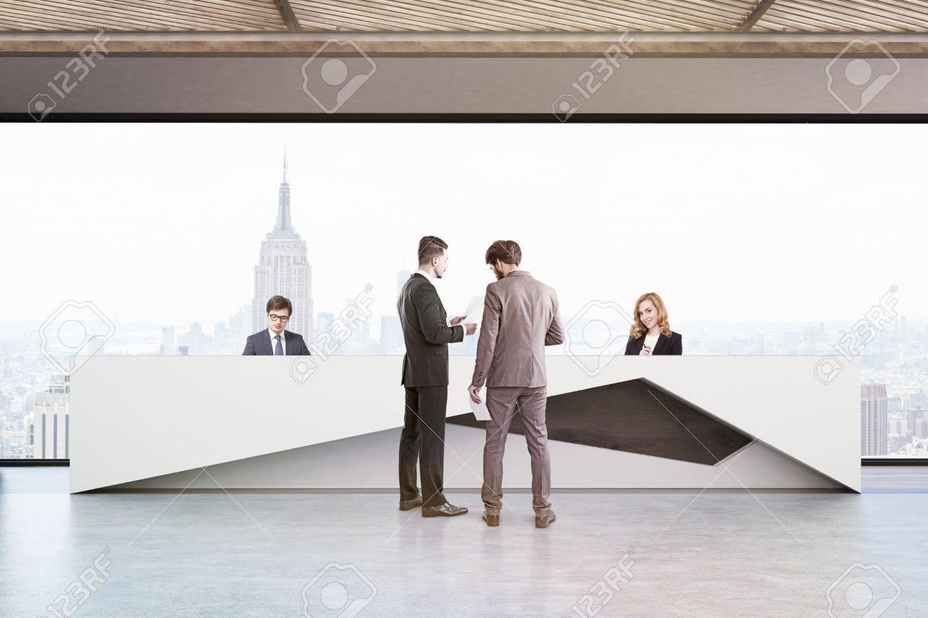 Les gens dans le bureau avec un grand comptoir de réception dans