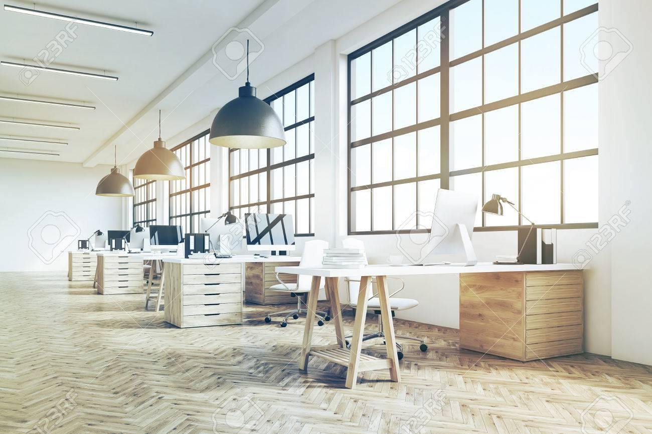 sitio de la oficina de largo con piso de madera mesas largas con grandes escritorios