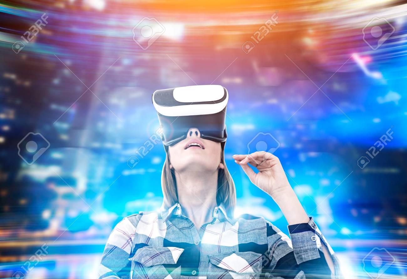 Banque d images - Portrait d une femme dans une chemise de flanelle portant  des lunettes de réalité virtuelle et debout dans un lieu holographique. e6ace5b9744a