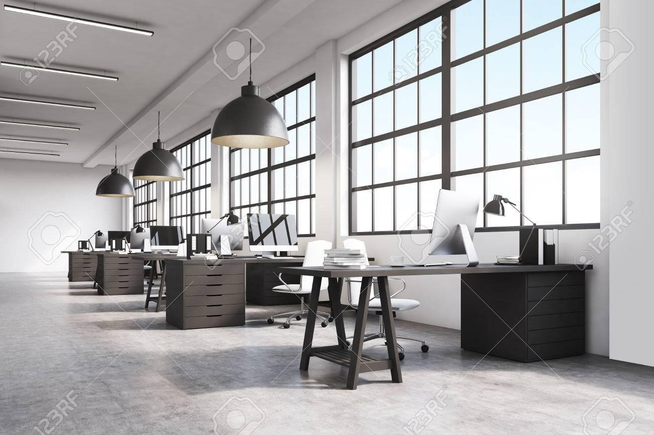 Intérieur bureau avec une rangée de tables en bois sombre debout