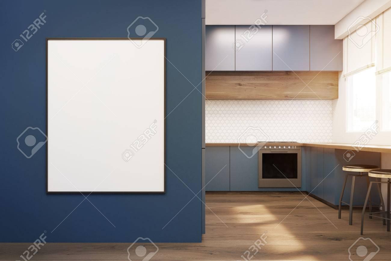 Interior cucina moderna con mobili blu, tavolo in legno e un forno. Un  poster incorniciato è appeso su una parete. Concetto di un appartamento ...